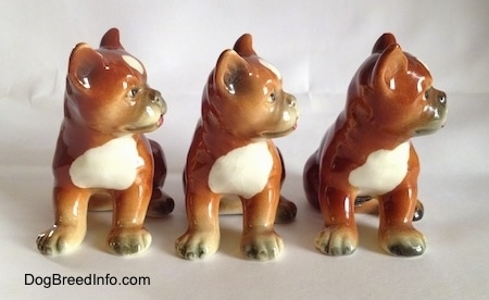 Three brown with white and black Boxer puppy figurines. The figurines have detailed eyes.