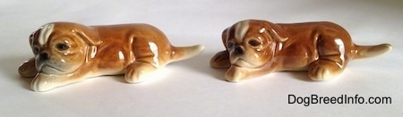 The left side of two brown with white Boxer puppy figurines and they both have detailed faces.