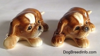 Two brown with white Boxer puppy figurines. The figurines have black circles for eyes.