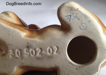 Close up - The underside of a Boxer puppy figurine. On the bottom there is a hole, above it is a Goebel W. Germany logo and to the left of the hole is the engraved number - 30502-02.