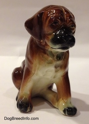 A brown with black and white ceramic Boxer puppy figurine with uncropped ears in a sitting pose. The figurine is very detailed.