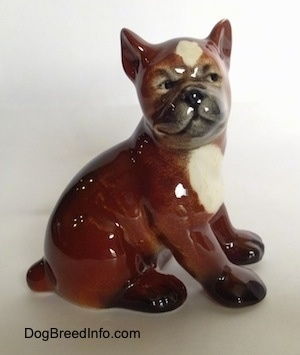 The right side of a brown with white and black Boxer puppy figurine. The figurine has a detailed face.