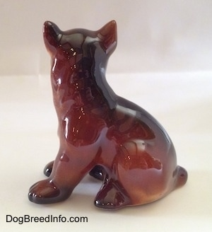 The left side of a brown with white and black Boxer puppy figurine. The figurine paws lack details.