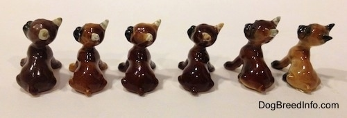 The back of a line-up of the different color variations of a Boxer puppy figurine that is in a sitting pose. The figurines are all glossy.