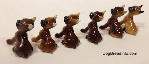 The back left side of a line-up of different color variations of a Boxer puppy figurine. All the figurines have black muzzles.