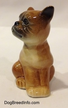 A brown with white Boxer puppy figurine that is in a sitting pose. The paws of the figurine are attached together.