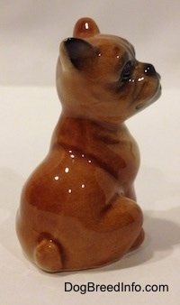 The back right side of a brown with white Boxer puppy figurine that is in a sitting pose. The figurine has a short tail.