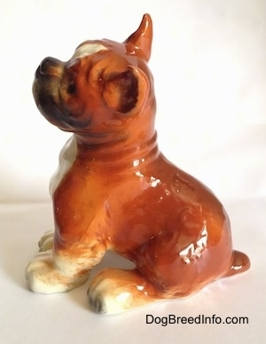 The left side of a porcelain brown with white and black Boxer dog figurine. The figurine has a detailed wrinkly neck.