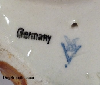 The underside of a porcelain brown with white and black Boxer dog figurine. There is the Goerbel W. Germany logo, above it is a hole and to the left of it is a stamp of the word - Germany.