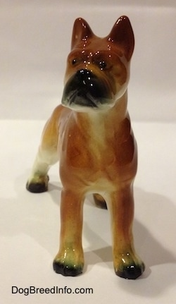 A brown with black and white ceramic Boxer dog figurine. The figurine has little black circles for eyes.