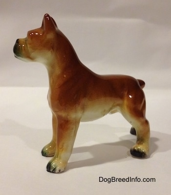 The left side of a brown with black and white ceramic Boxer dog figurine. The figurine has a detailed body and legs.