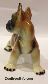 A brown with white and black porcelain Boxer dog figurine.