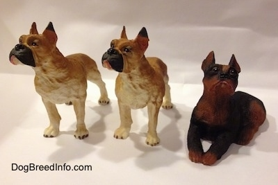 Two tan with white and black Boxer figurines are placed next to a black with brown laying Boxer figurine.