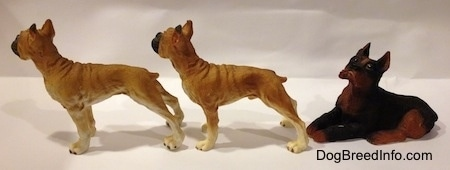 The left side of two tan with white and black Boxer standing figurines are in front of a black with brown laying Boxer figurine.