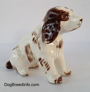 The right side of a brown and white ceramic Brittany Spaniel that is in a sitting pose. The ears of the figurine has great details.