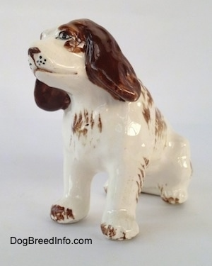 The front left side of a brown and white ceramic Brittany Spaniel that is in a sitting pose. The figurine has black whisker dots on its muzzle and detailed painted eyes.