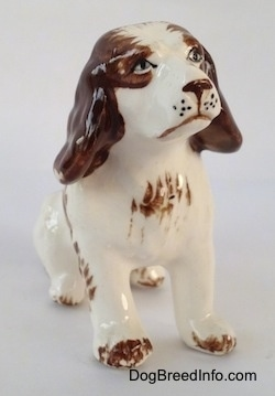 A ceramic brown and white Brittany Spaniel figurine that is in a sitting pose. The figurine has brown paw tips.