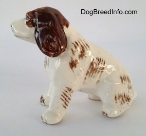 The left side of a brown and white ceramic Brittany Spaniel that is in a sitting pose. The figurine is glossy. The brown ears hang down to the sides.