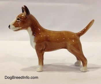 The left side of a brown with white Bull Terrier figurine. The paws of the figurine are white. The dog has perk ears and a tail that stands up. It has a black nose.