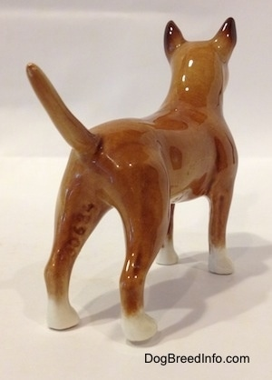 The back right side of a brown with white Bull Terrier figurine. The figurines tail is arched up.