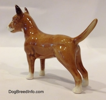 The back left side of a brown with white Bull Terrier figurine. The figurines tail is long.