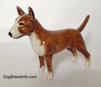 The left side of a brown with white Bull Terrier figurine. The figurine has circles for eyes.