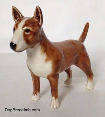 The front left side of a brown with white Bull Terrier figurine. The figurine has white paws and black painted eyes. Its tail is up in the air.