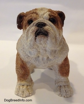 A brown and white ceramic mold of a Bulldog figurine. The figurine has black circles for eyes.