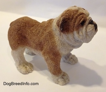 The right side of a brown and white ceramic mold of a Bulldog figurine. The paws of the figurine have fine details.