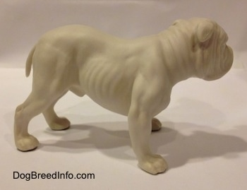The right side of a white bisque porcelain Bulldog figurine. The figurine has a detailed body.