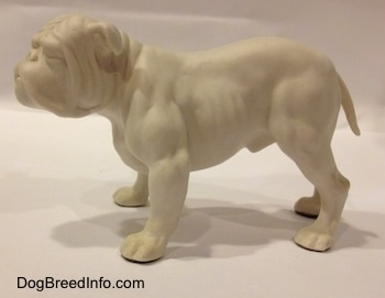The left side of a white bisque porcelain Bulldog figurine. The figurine has a medium length tail.