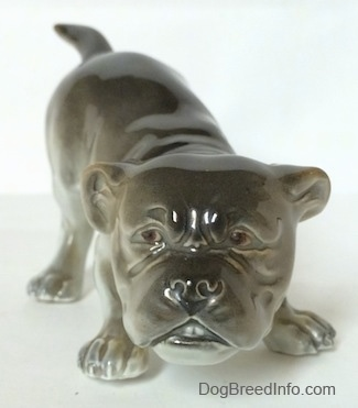 A gray and white Bulldog figurine in a play bow pose. The figurine has a slightly detailed face.