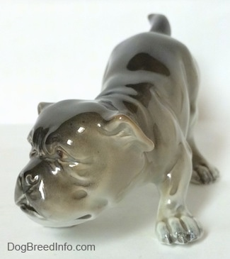 The front left side of a gray and white Bulldog figurine in a play bow pose. The paws of the figurine have fine details.