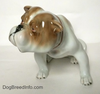 A white with brown Bulldog figurine in a sitting pose.