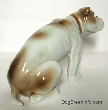 The back right side of a white with brown Bulldog figurine in a sitting pose. The figurine has very detailed paws.