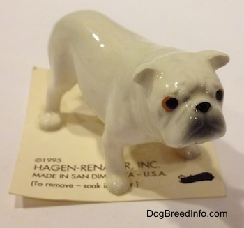 A white miniature Bulldog figurine. The figurine has copper and black eyes.