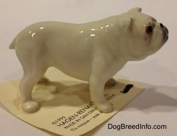 The right side of a white miniature Bulldog figurine. The figurines ears are hard to differentiate from the head.