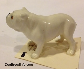 The left side of a white miniature Bulldog figurine. The figurine is glossy.