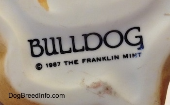 Close up - On the underside of a Bulldog puppy figurine there is a stamp that reads - BULLDOG © 1987 The Franklin Mint.