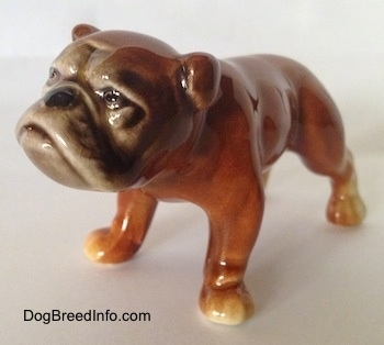 The front left side of a brown Bulldog figurine. The figurines paws have subtle details.