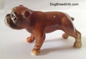 The left side of a brown Bulldog figurine. The tail of the figurine is short and it is sticking out.