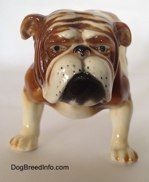 A brown and white Bulldog figurine that has black circles for eyes and black whisker spots.