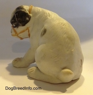 The back of a white with black bone china Bulldog puppy figurine that has a muzzle on it. The figurine has a small tail.