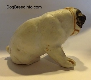The right side of a white with black bone china Bulldog puppy figurine that has a muzzle on it. The figurine has fine paw details.