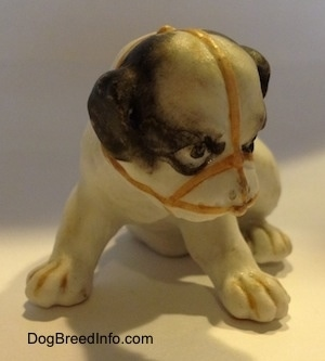 A white with black bone china Bulldog puppy figurine that has a muzzle on it.