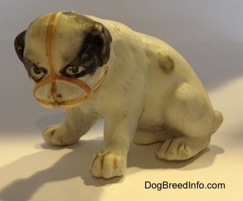 The left side of a white with black bone china Bulldog puppy figurine that has a muzzle on it. The figurine has black circles for eyes.