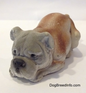 A cement mold paperweight made that is a brown with white English Bulldog figurine that is laying down. The figurine has great face details.