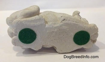 The underside of a cement mold paperweight made that is a brown with white English Bulldog figurine that is laying down. There are two green stickers at the bottom of the figurine.