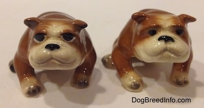 Two brown with white miniature Bulldogs that are in a sitting pose. The figurines have black circles for eyes.