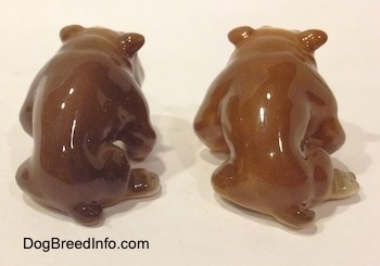 The back side of two brown with white miniature Bulldogs that are in a sitting pose. The figurines have short tails.